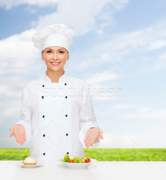 smiling female chef with salad and cake on plates Stock photo © dolgachov