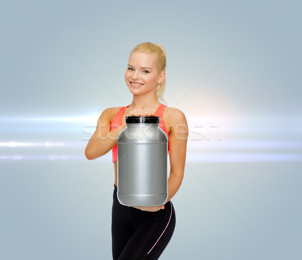 smiling sporty woman with jar of protein Stock photo © dolgachov