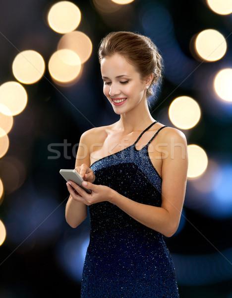 улыбающаяся женщина вечернее платье смартфон технологий связи праздников Сток-фото © dolgachov