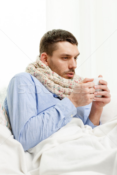 man in scarf holding cup with hot drink at home Stock photo © dolgachov