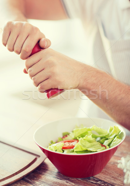 close up of male hands flavouring salad in a bowl Stock photo © dolgachov