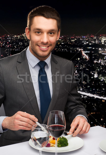 Stock photo: smiling man eating main course