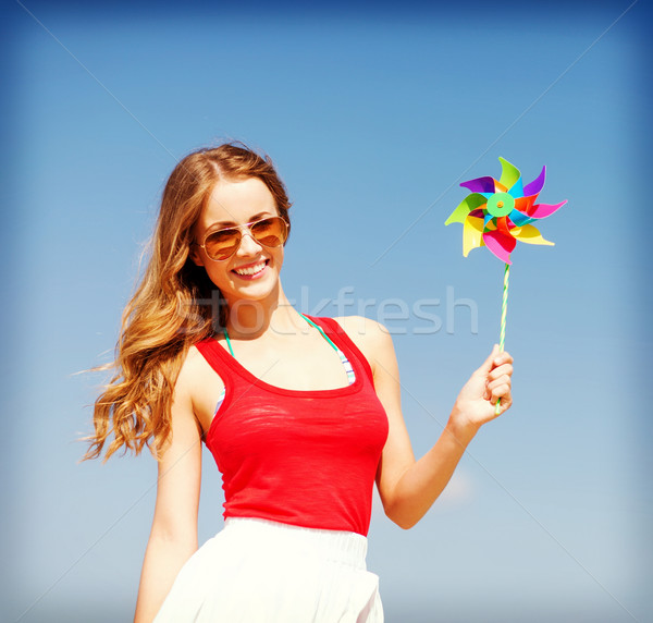 Stock photo: girl with windmill toy on the beach