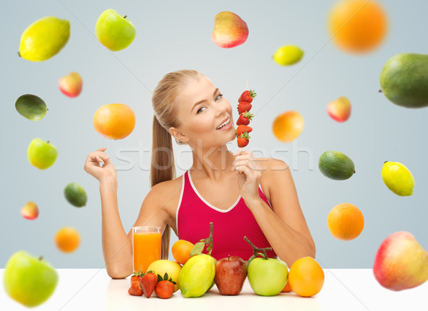 woman with juice and fruits eating strawberries Stock photo © dolgachov