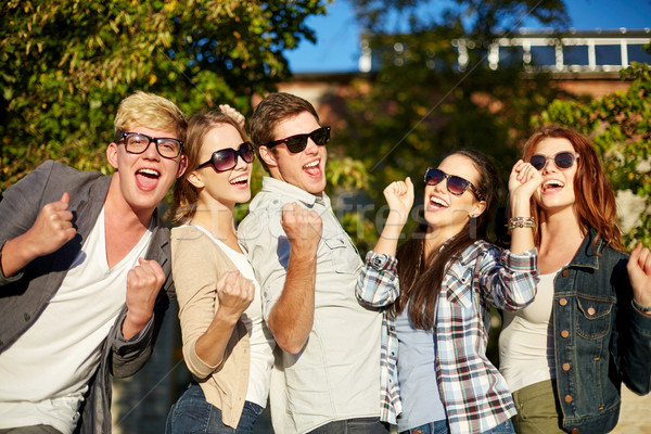 Groupe heureux amis triomphe geste Photo stock © dolgachov
