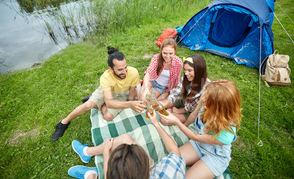 happy friends with tent and drinks at campsite Stock photo © dolgachov