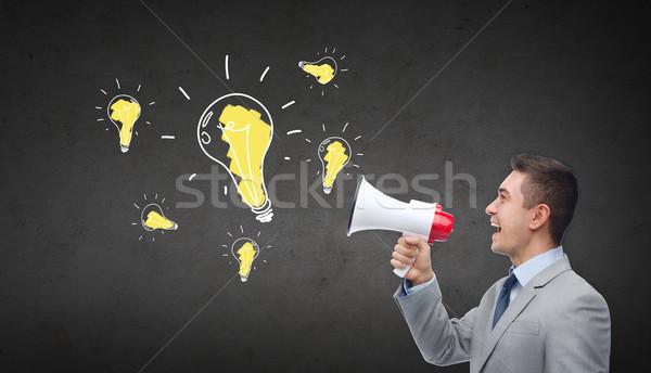happy businessman in suit speaking to megaphone Stock photo © dolgachov