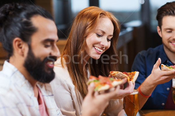 friends eating pizza with beer at restaurant Stock photo © dolgachov