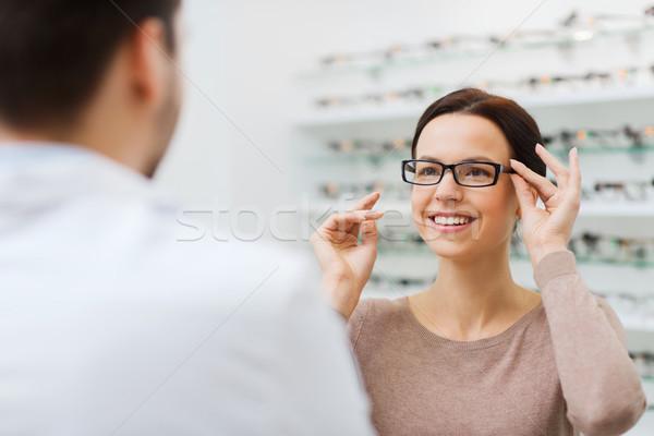 Mulher escolher óculos ótica armazenar Foto stock © dolgachov