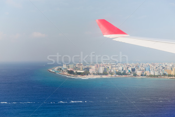 close up of airplane wing above Maldives and ocean Stock photo © dolgachov