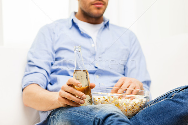 close up of man with popcorn and beer at home Stock photo © dolgachov