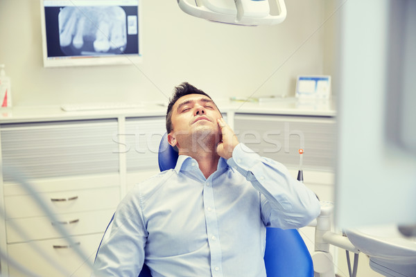man having toothache and sitting on dental chair Stock photo © dolgachov