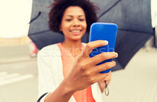 Vrouw paraplu smartphone business slechte weer Stockfoto © dolgachov