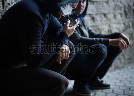 Stock photo: close up of young men smoking cigarettes