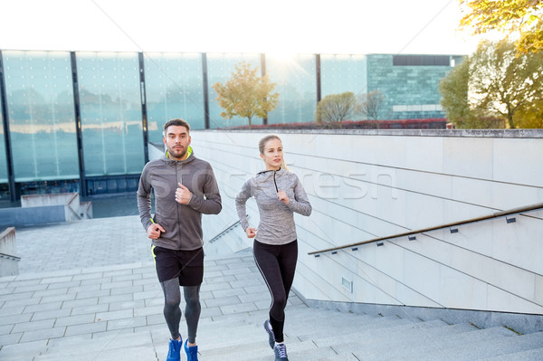 happy couple running upstairs on city stairs Stock photo © dolgachov