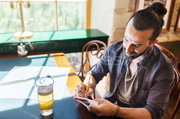 Man bier schrijven notebook bar pub Stockfoto © dolgachov