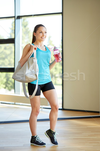 woman with sports bag and bottle of water in gym Stock photo © dolgachov