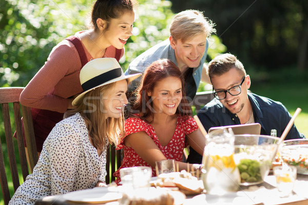 friends with tablet pc at dinner in summer garden Stock photo © dolgachov