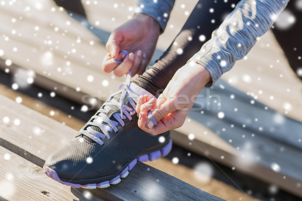 Stock photo: close up of sporty woman tying shoelaces outdoors