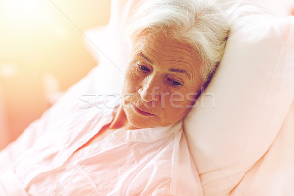 senior woman patient lying in bed at hospital ward Stock photo © dolgachov