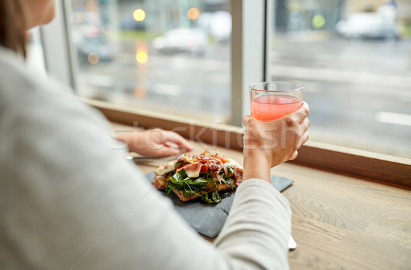 woman with salad and glass of drink at restaurant Stock photo © dolgachov