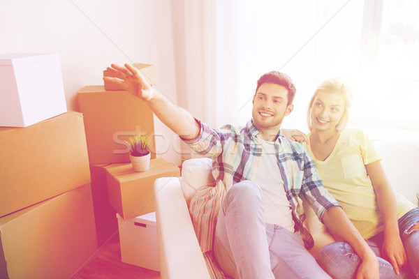 couple with boxes moving to new home and dreaming Stock photo © dolgachov