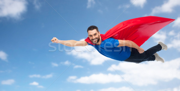 happy man in red superhero cape flying over sky Stock photo © dolgachov