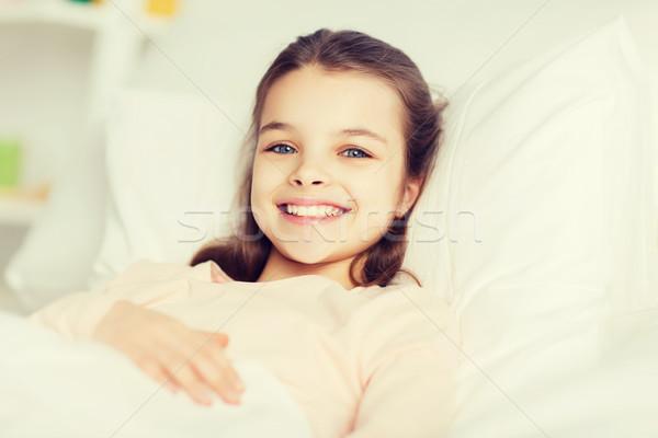 幸せ 笑みを浮かべて 少女 目が覚める ベッド ホーム ストックフォト © dolgachov
