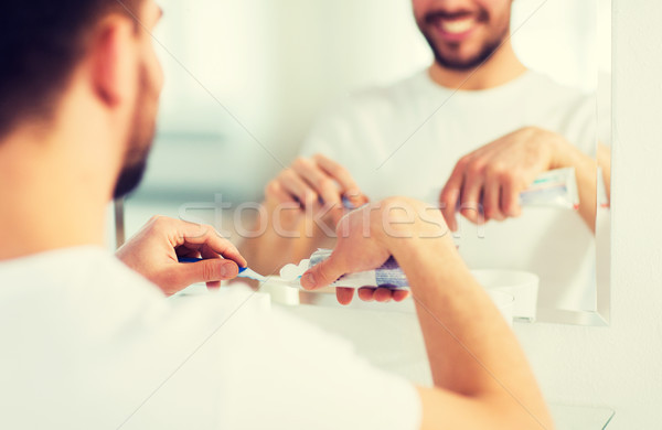 close up of man squeezing toothpaste on toothbrush Stock photo © dolgachov