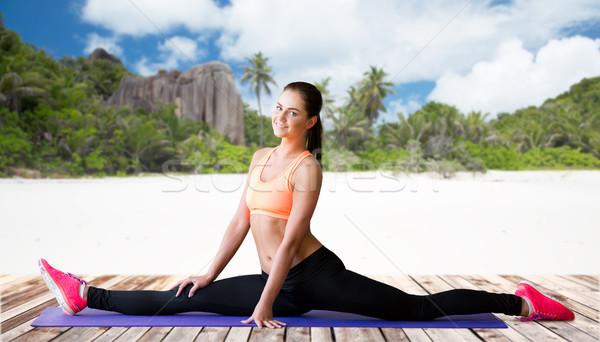smiling woman doing splits on mat over beach Stock photo © dolgachov
