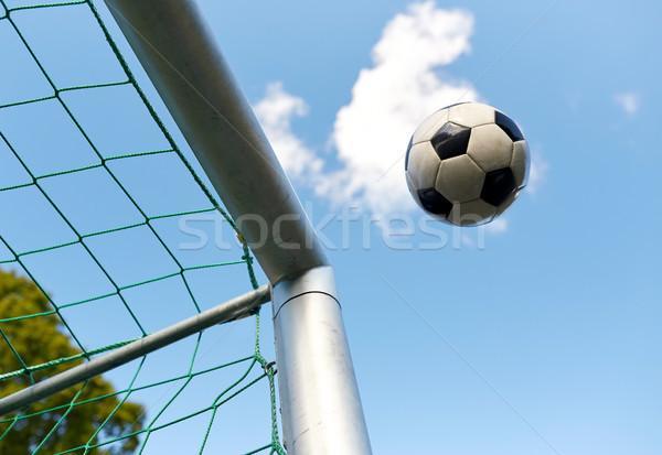 soccer ball flying into football goal net over sky Stock photo © dolgachov
