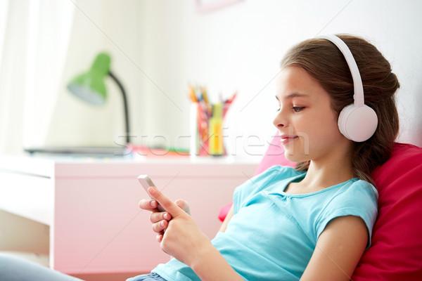 快樂的女孩 智能手機 頭戴耳機 家 孩子 技術 商業照片 © dolgachov