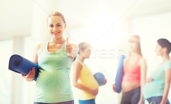 pregnant woman with mat in gym showing thumbs up  Stock photo © dolgachov