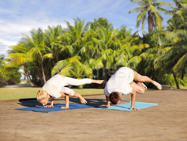 couple making yoga side crane pose outdoors Stock photo © dolgachov