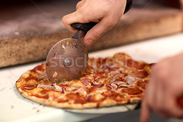cook hands cutting pizza to pieces at pizzeria Stock photo © dolgachov