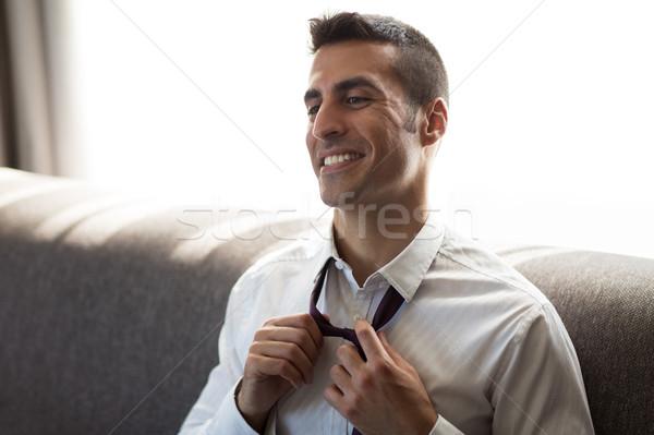happy businessman taking off his tie at hotel room Stock photo © dolgachov