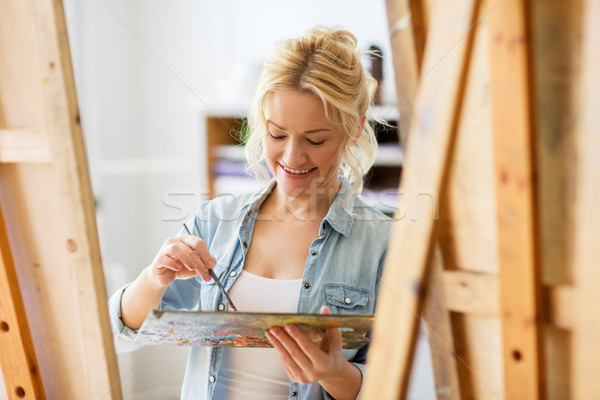 happy woman with easel painting at art school Stock photo © dolgachov