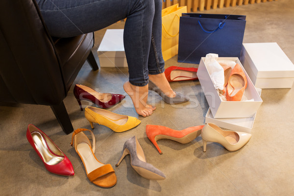 young woman trying and choosing shoes at store Stock photo © dolgachov