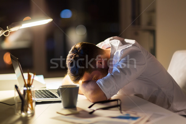 tired businessman lying on table at night office Stock photo © dolgachov