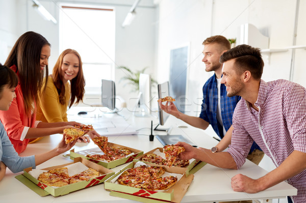 Stock photo: happy business team eating pizza at office