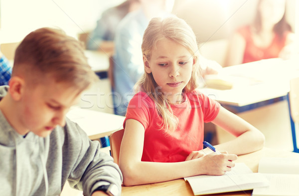 group of students with books writing school test Stock photo © dolgachov