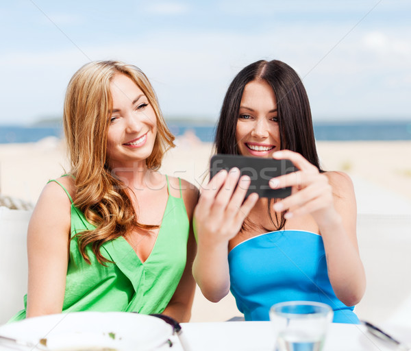 girls taking photo in cafe on the beach Stock photo © dolgachov