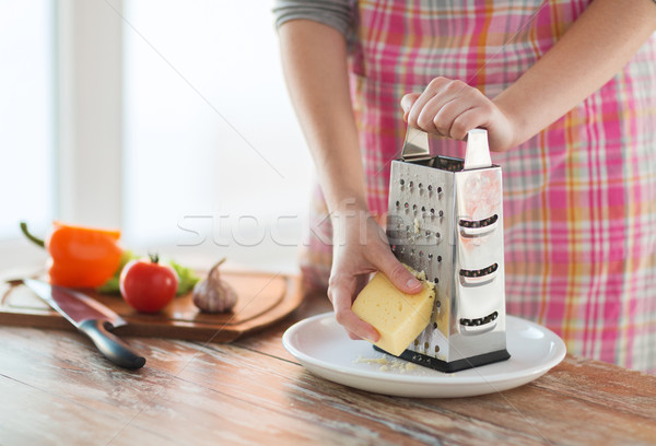 close up of female hands grating cheese Stock photo © dolgachov