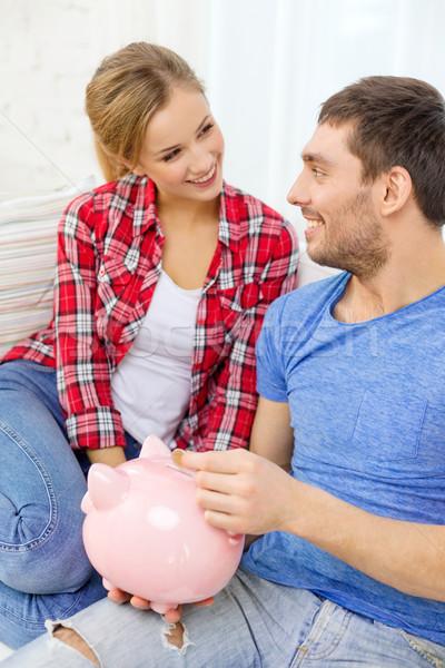 smiling couple with piggybank sitting on sofa Stock photo © dolgachov