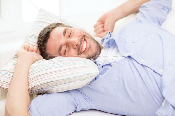 smiling young man lying on sofa at home Stock photo © dolgachov