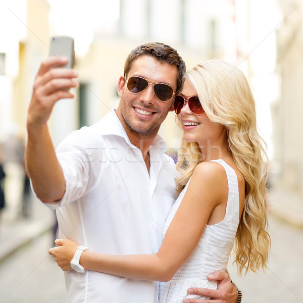Stock photo: smiling couple taking selfie with smartphone