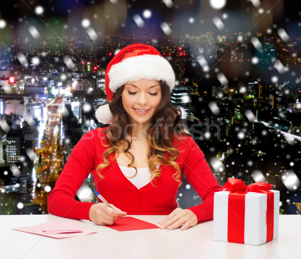 smiling woman with gift box writing letter Stock photo © dolgachov