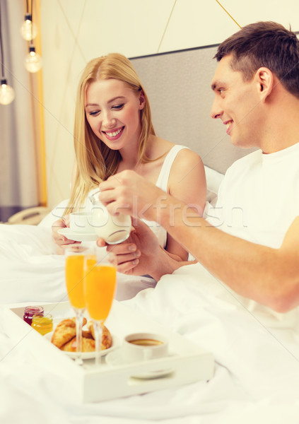 smiling couple having breakfast in bed in hotel Stock photo © dolgachov