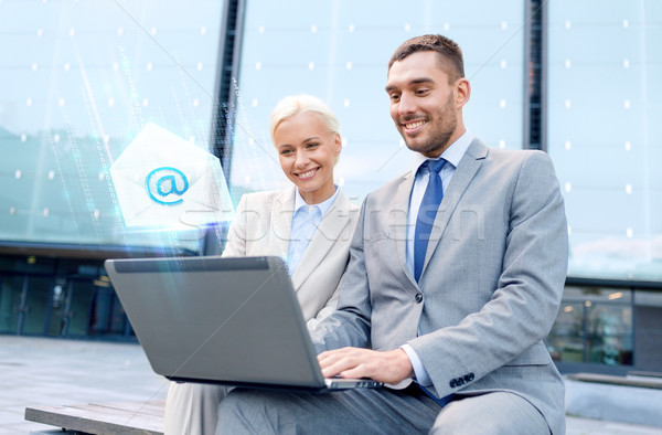 smiling businesspeople with laptop sending e-mail Stock photo © dolgachov