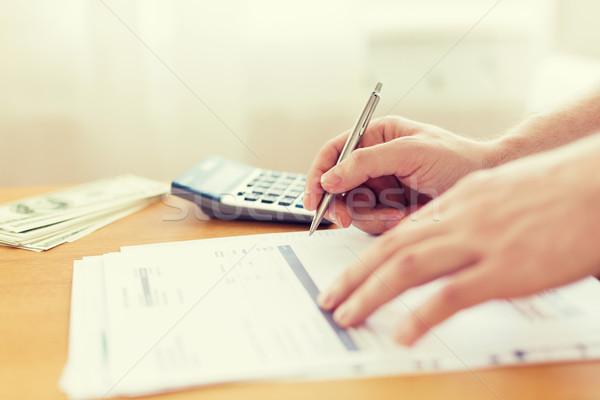 close up of man counting money and making notes Stock photo © dolgachov